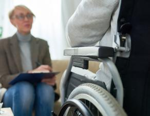 Une personne handicapée dans un fauteuil roulant devant une femme