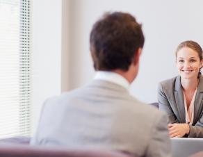 Une femme souriante en face d'un homme au travail