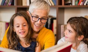 Une femme moyennement agée fait la lecture à deux fillettes