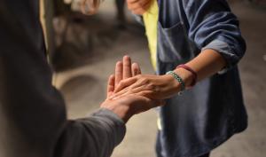 Un enfant tient la main d'une personne âgée