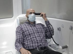 Un homme prend sa température dans une cabine de téléconsultation