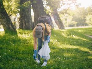 Une femme ramasse un déchet dans une forêt