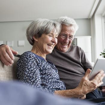 Une femme et un homme âgés sourient et utilisent une tablette