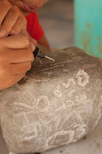 Un enfant grave une pierre