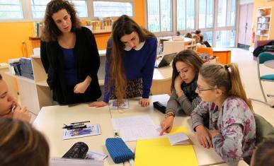 Des enseignants et des collégiens en groupe de travail en classe