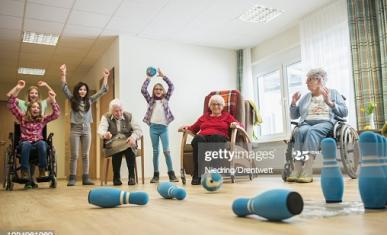 Des pesonnes âgées en fauteuil roulant jouent avec des jeunes enfants