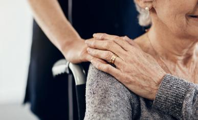 Main d'une jeune femme posée sur l'épaule d'une femme âgées en fauteuil