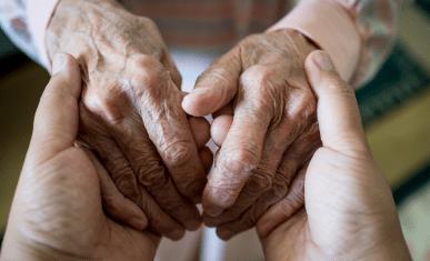 Gros plan sur les mains d'une personne âgée tenues par les mains d'une personne plus jeune