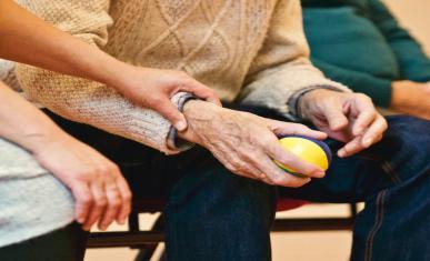 Une personne prend soin d'une personnes âgées en le touchant.