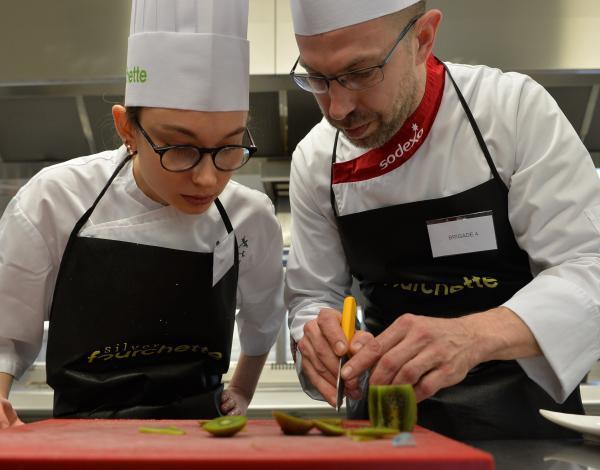 Un cuisinier montre un geste pro à une apprentie