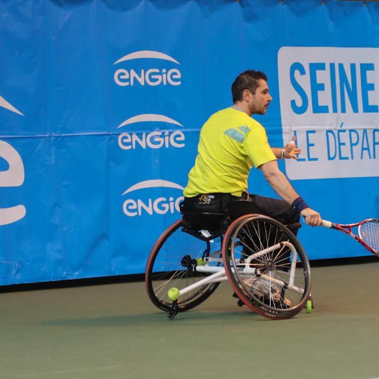 Un joueur de tennis en fauteuil roulant en train de jouer