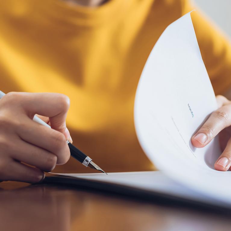 Une femme en train de signer un contrat