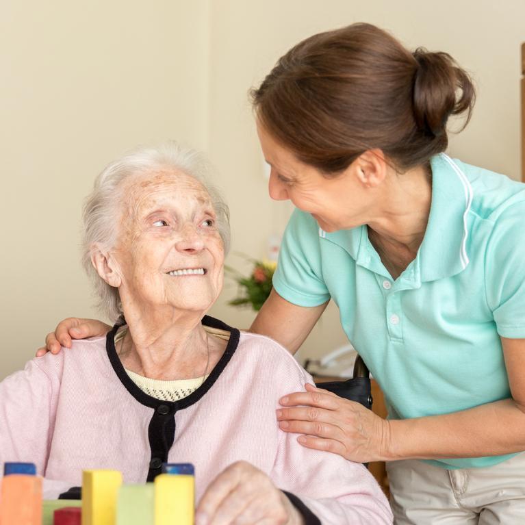 Une femme âgée en train de faire un jeu de mémoire entouré d'une jeune femme aidante