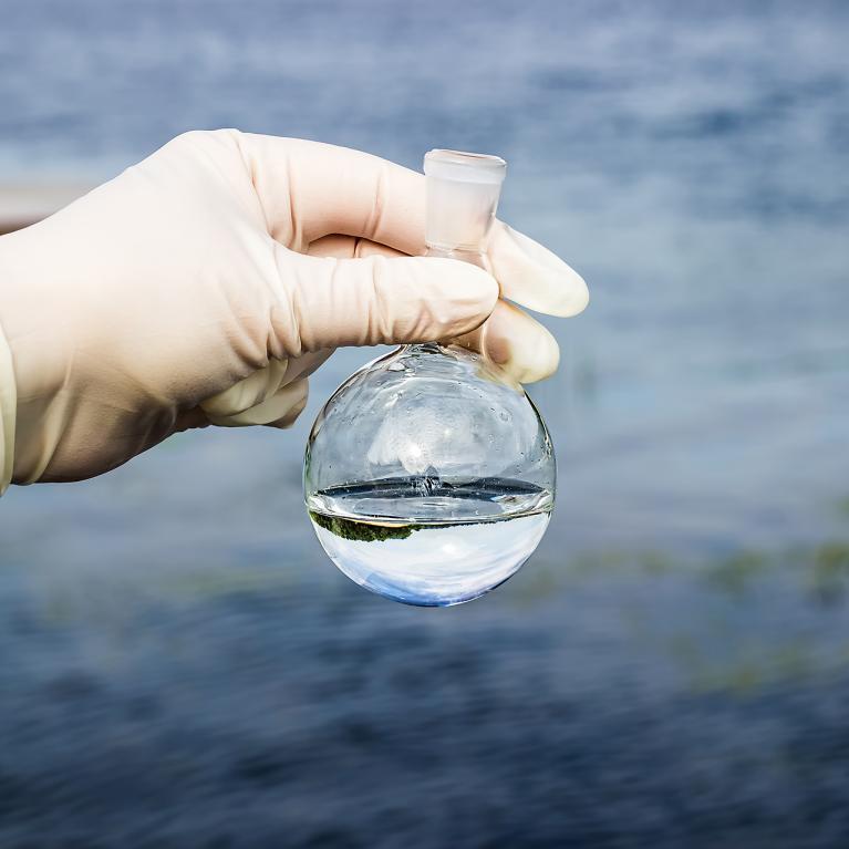 Une main gantée tient un contenant empli d'eau avec en fond un étendue d'eau