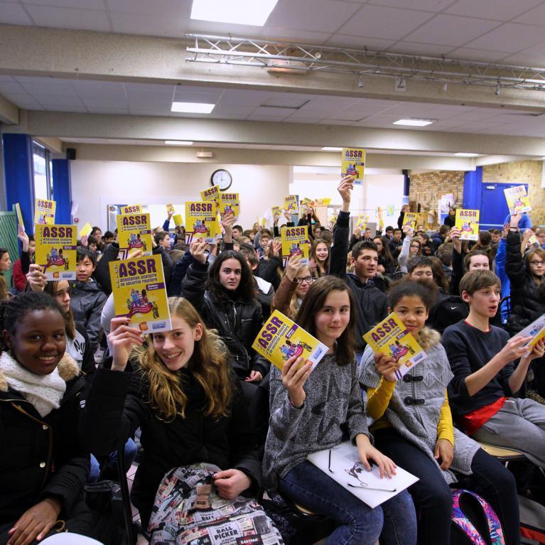 Des collégiens réunis dans une salle brandissent leur attestation scolaire de sécurité routière