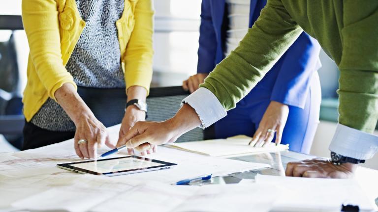 Une équipe de travail devant une tablette numérique