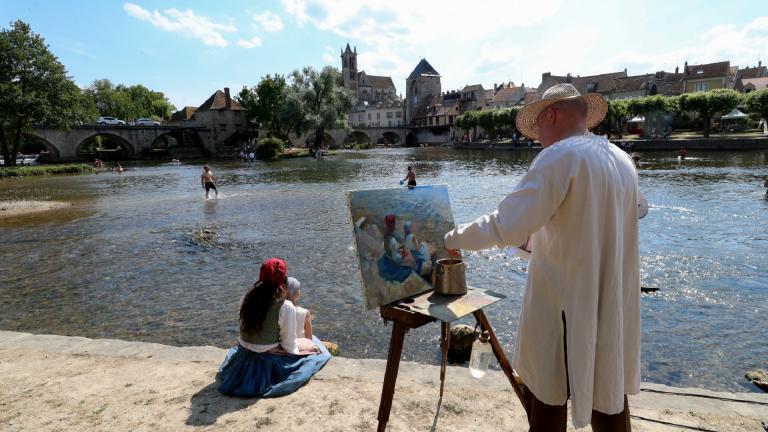 Un artiste peint une femme et un enfant au bord de l'eau