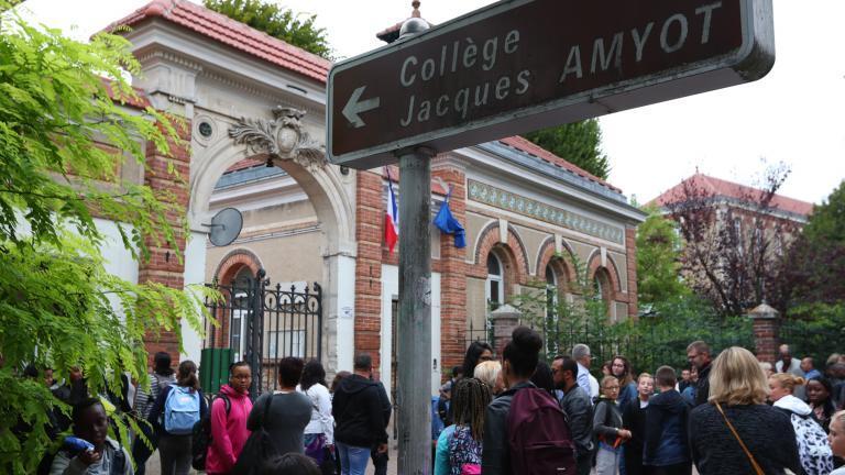 Des élèves sont groupés devant l'entrée du lycée Jacques Amyot