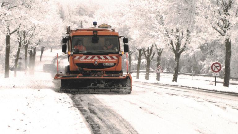 Camion de déneigement sur route enneigée