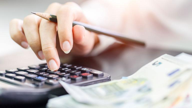 Une personne tape sur une calculatrice pour faire ses comptes