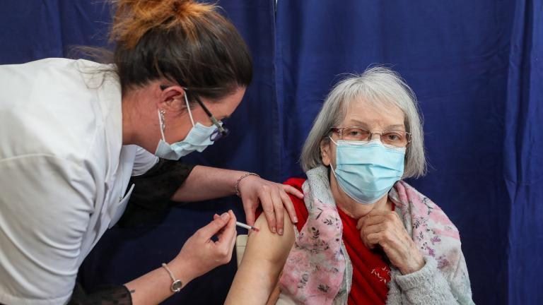 Un médecin vaccine une personne âgée