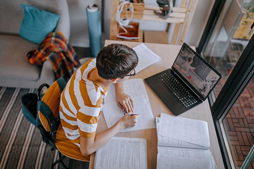 Un adolescent faisant ses devoirs devant son ordinateur dans sa chambre