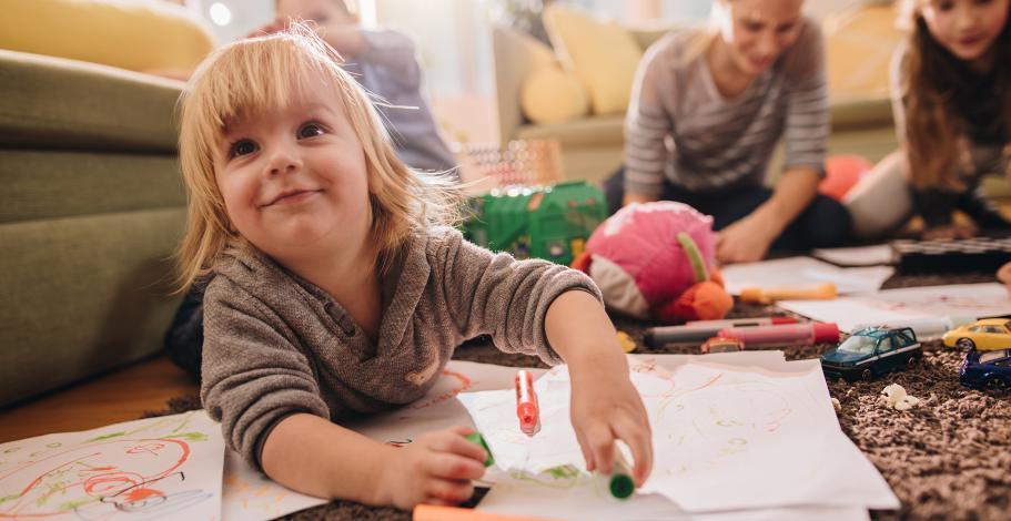 Des enfants parterre en train de dessiner sur des pages sous la surveillance d'une nounou